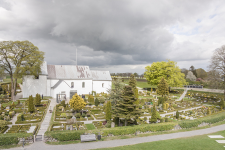 JELLING, DENMARK - MAY 9, 2017:  White church on the monument area which enjoys UNESCO World Heritage patronage on may 9, 2017 in Jelling, Denmark. Editorial