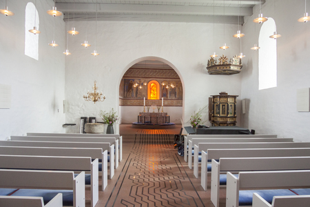 JELLING, DENMARK - MAY 9, 2017: Interior of white church on the monument area which enjoys UNESCO World Heritage patronage on may 9, 2017 in Jelling, Denmark.