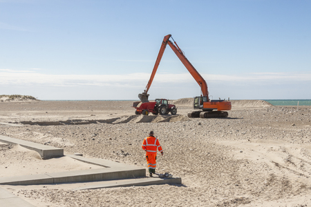 Excavator on the beach in Norre Vorupor, Denmark, Europe.