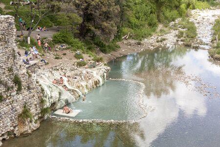 MONTICIANO, ITALY - APRIL 30, 2019: Tourist in hot springs Bagni di Petriolo  on April 30,2019 in Monticiano in Italy. 写真素材 - 129998771