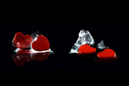 Four hearts in almost melted ice cubes with  reflection on black background photo