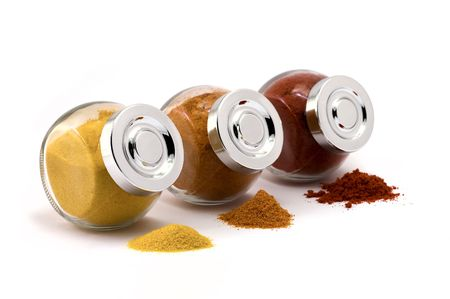 Three jars with spices on isolated white background, focus at closest jar cap photo