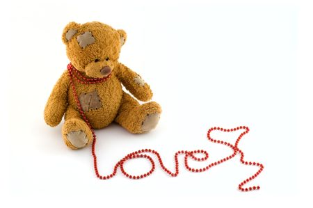 Sweet teddy bear with a string of red beads arranged to love at isolated white background Stock Photo
