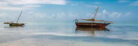 Zanzibar in Tanzania, typical fishing boat on a beautiful beach with waves