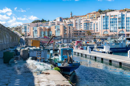 Sète in France, fisherboat at the quay, typical colorful facades in the harbor