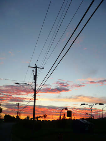 an electric pole in town during a sunset