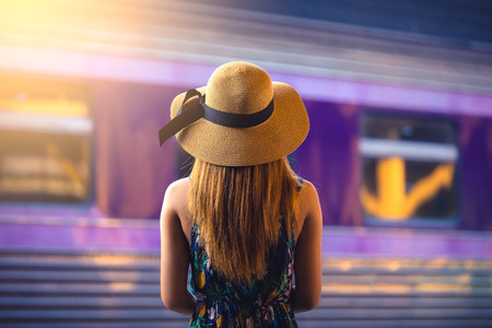 Woman with hat near railroad tracks waiting for train
