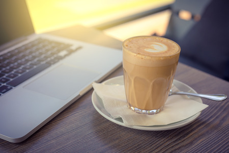 coffee capuccino and laptop with morning light on cafe terrace , hot drink