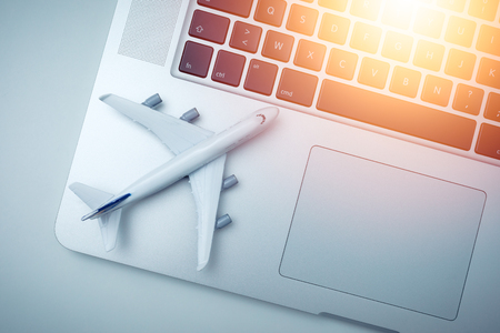 bright picture of a white plane model and computer laptop with sunlight on white background . travel , visa and vacation concept Banco de Imagens