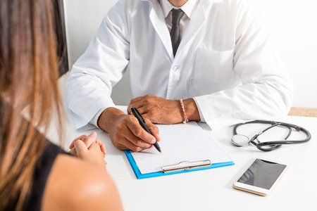 Doctor and patient are discussing about diagnosis. Medical doctor holding a stethoscope, looking at medical form and taking notes.