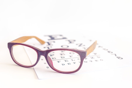Close up of a eyeglasses on eye chart background , Myopia or hyperopia concept Stock Photo