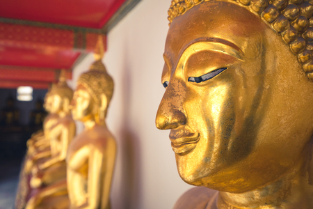 close up of a golden buddha head in wat pho temple in Bangkok , Thailand , asia