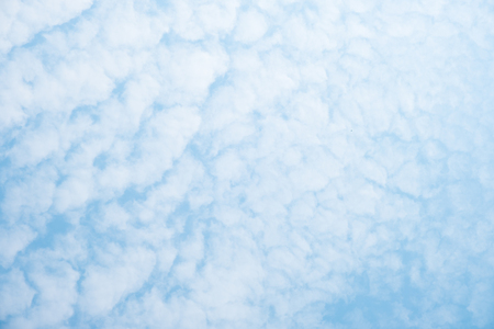 Blue sky background with white clouds during a sunny day .