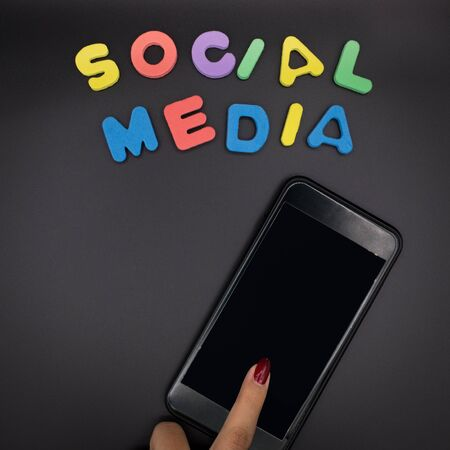 dark image of woman using phone with social media letters , smart phone on black background . social media concept