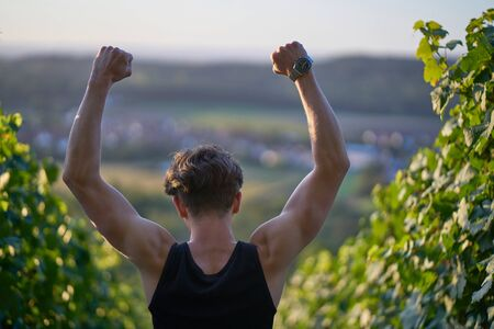 Young sporty skinny man in tank top raising fists and arms in winner pose in vineyards