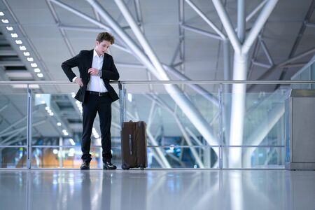 Young businessman standing inside the airport in front of a glass guard railing with his rolling case, searching something in his suit pocket