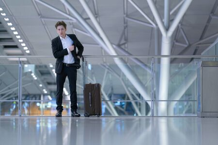Young businessman standing inside the airport in front of a glass guard railing with his rolling case, searching something in his suit pocket Stok Fotoğraf - 133972369