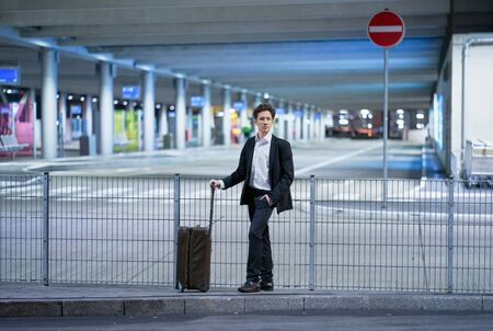 Young businessman waiting outside the airport with his rolling suitcase, one hand in his pocket Stok Fotoğraf - 133972367