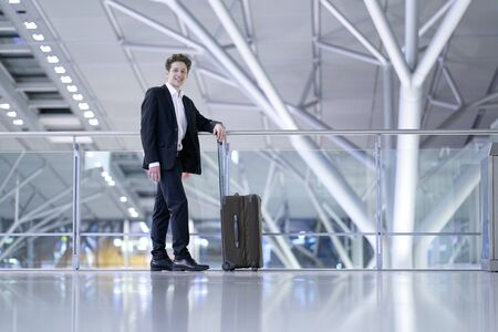 Young relaxed smiling businessman standing with his rolling suitcase in the airport, leaning with his arm on a guard railing Stok Fotoğraf - 133972368