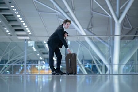 Young handsome businessman wearing a suit standing at the glass guard railing inside an airport with his hands at his rolling suitcase Stok Fotoğraf - 133972375