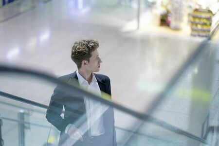 Young businessman in a suit on an escalator in a business building, with light reflections 版權商用圖片