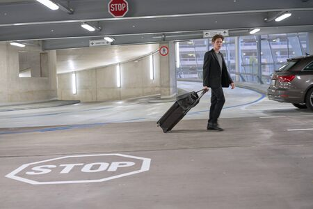 Young businessman walking to his rental car through car parking on airport 版權商用圖片