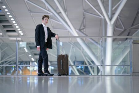 Young relaxed smiling businessman standing with his rolling suitcase in the airport, leaning with his arm on a guard railing
