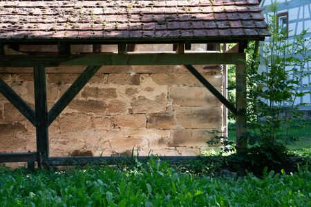 Close up of a stone shelter with timber frame in green nature