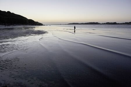 Lonely boy standing in the shallow water of a bay, dusk mood, loneliness