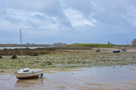Coast in Brittany at low tide with sand and seaweed and small boats, cloudy blue sky