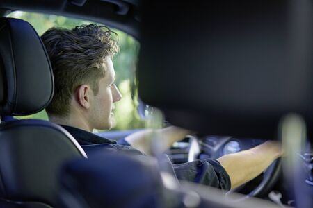Close up of a young driver in his car with hands on the wheel