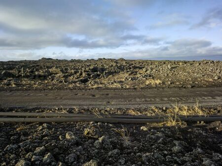 Gravel road in volcanic dramatic area in Iceland with pipeline. Backplate for offroad 4x4 4WD cars.