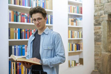 Young man with glasses in library standing next to bookshelf while he is looking into the camera Stok Fotoğraf - 137731189