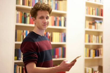Teenager in library staying in front of bookshelf with smartphone in his hand