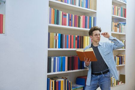 Young student next to bookshelf with book in hand checking his glasses
