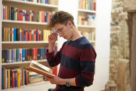 Young concentrated student with glasses reading a book in library in front of bookshelf. Stone wall in background. Stok Fotoğraf