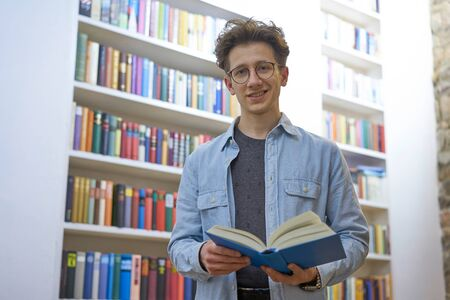 Friendly, smiling man with glasses, staying in library, with a book in his hands Stok Fotoğraf
