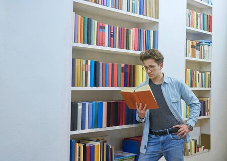 Young man reading a book while leaning on a bookshelf with colorful books in a library.