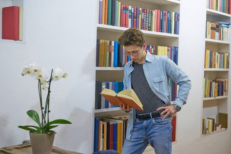 Young man with a watch, glasses and a  ring on his finger lost in reading in front of a bookshelf. Orchid in the foreground.