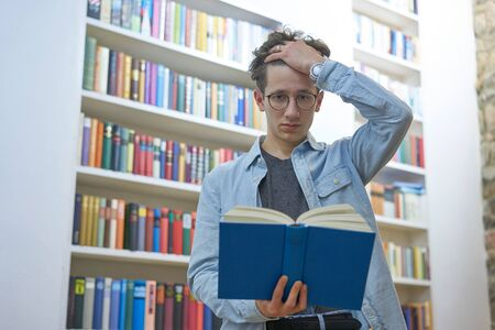 Young, overcharged student with glasses, tearing his hair while reading in library at university. Stok Fotoğraf - 137847911
