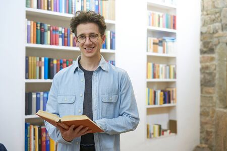 Portrait of a young man with glasses, smiling with book in his hands in university Stok Fotoğraf