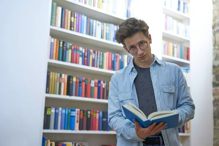 Serious young man with glasses, looking up from reading, next to a bookshelf Stok Fotoğraf - 137847078