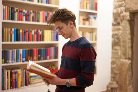 Satisfied young man with glasses, reading a book in front of a bookshelf in library.