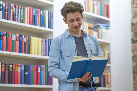 Young man in library finding the book he is reading very amusing. Stok Fotoğraf - 137847673