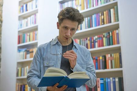 Pensive young man with book in his hand and glasses in his mouth, standing in library, next to bookshelf. Stok Fotoğraf