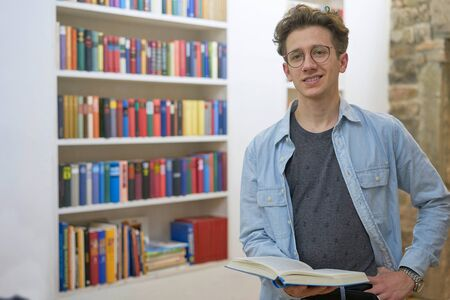 Friendly smiling teenager with glasses holding a book in his hands in a home library of a loft. Stok Fotoğraf