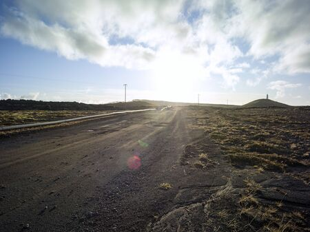 Gravel road in a volcanic landscape with moss in Iceland. Pipeline next to gravel road. Backplate for offroad 4x4 4WD cars. Backplate for trekking and hiking. Blue sky with clouds.