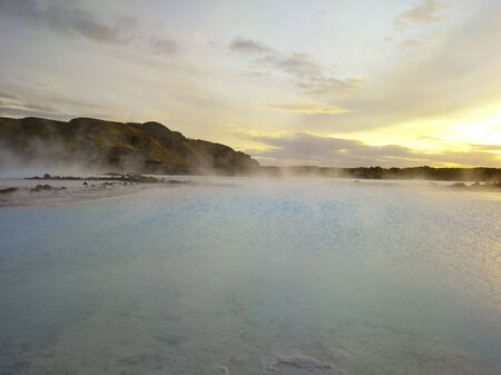 Beautiful landscape of Blue Lagoon thermal bath in Iceland with steam in a cold atmosphere in sunset with a dramatic sky.