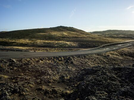 Gravel road in a volcanic landscape with moss in Iceland. Pipeline in the foreground next to gravel road. Backplate for offroad 4x4 4WD cars. Backplate for trekking and hiking. Blue sky.