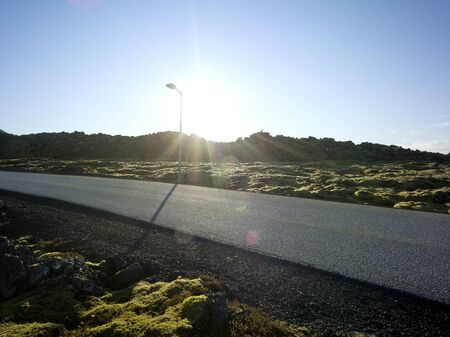Black tarmac country road in a landscape in Iceland with moss and gravel. Backplate for car industry and cgi.